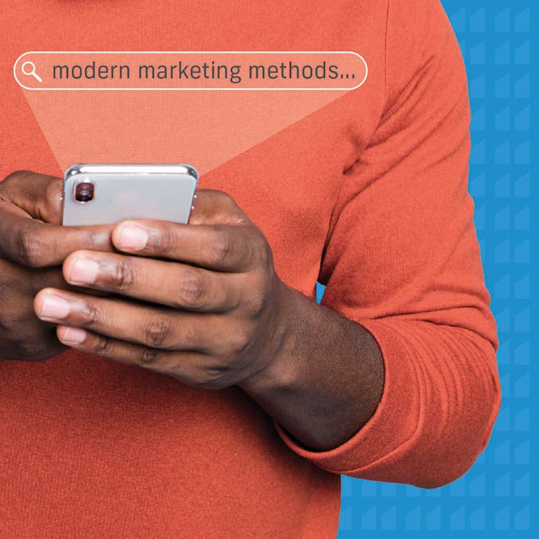 """Man in an orange shirt with a blue background holding a phone with text reading, """"modern marketing methods""""."""